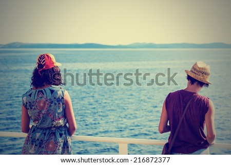 Two female passengers on the deck of the ferry watching the Adriatic Sea in Croatia; post processed instagram retro style - stock photo
