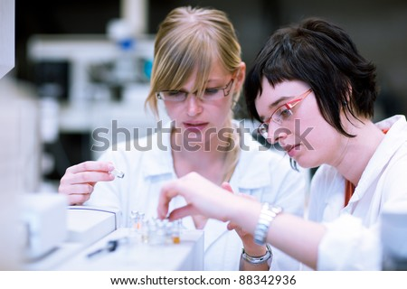 two female researchers/chemistry students doing research in a chemistry lab (color toned image; shallow DOF) - stock photo