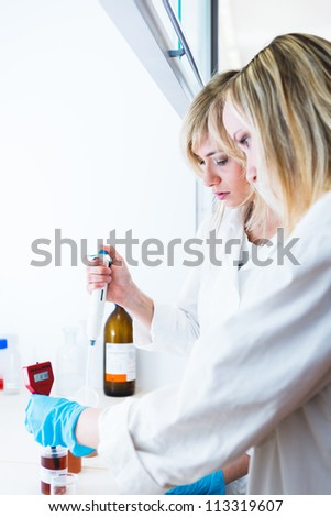 Two female researchers working in a laboratory (color toned image) - stock photo