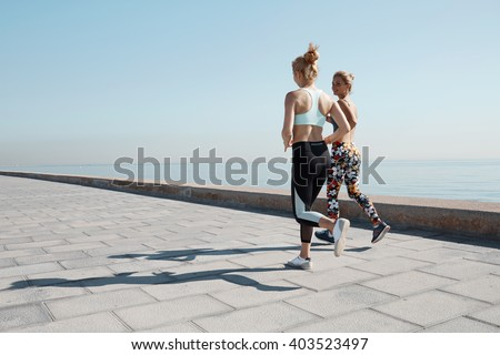 Two female runners exercising outdoors training together for marathon. Caucasian running partners working out outdoors on sunny day. Two fit joggers talking and smiling during workout on the beach.  - stock photo