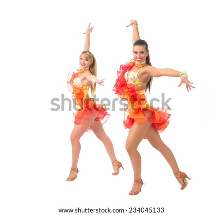 Two female salsa dancers in colorful dresses over white background - stock photo