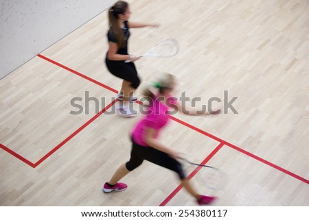 Two female squash players in fast action on a squash court (motion blurred image; color toned image) - stock photo