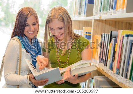 Two female students at school library standing and reading book - stock photo
