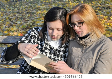two female students resting in the autumn  park , in series - stock photo