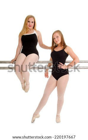 Two Female Teenage Ballet Dance Students in Soft Slipper Wait at the Barre - stock photo