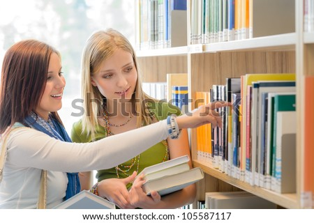 Two female teenage girls looking for book in school library - stock photo