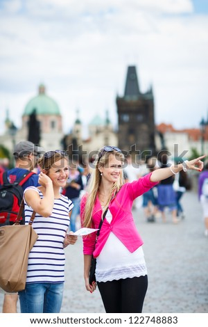 Two female tourists walking along the Charles Bridge while sightseeing in Prague, the historical capital of the Czech Republic (color toned image; shallow DOF) - stock photo