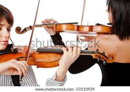 Two female violinists playing violins isolated on white - stock photo