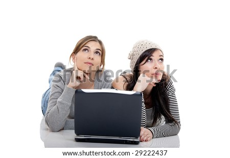 Two female young students working with a laptop - stock photo