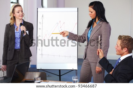 Two females standing and present graph on flipchart during business meeting, have an argue with male sitting at conference table - stock photo