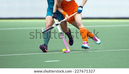 Two field hockey player, fighting for the ball on the midfield during an intense match on artificial grass - stock photo