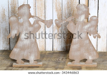 Two figure of an angel with a trumpet made wood. Christmas angel on a wooden background - stock photo