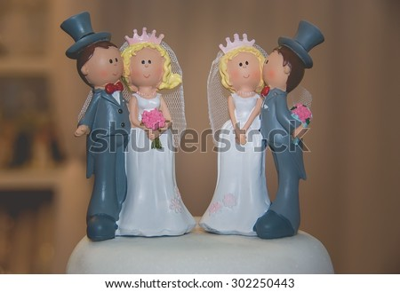 Two figurines of the bride and groom on the top of wedding cake - stock photo