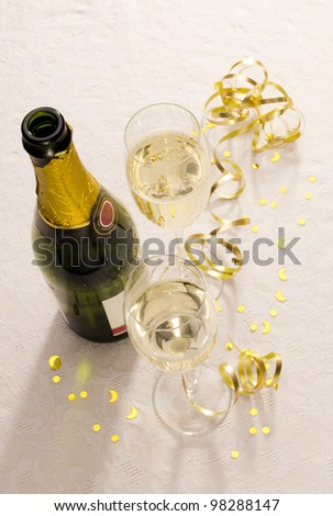Two filled champagne flutes and bottle from above on a tablecloth with gold ribbon and ornaments. - stock photo
