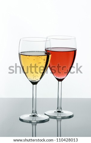 Two filled glasses on white background. - stock photo