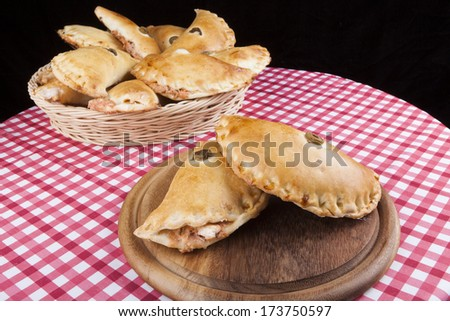 Two Filled pastry on wood plate with full basket in the background - stock photo