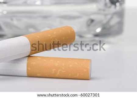 Two filtered cigarettes laying in front of a glass ashtray. - stock photo