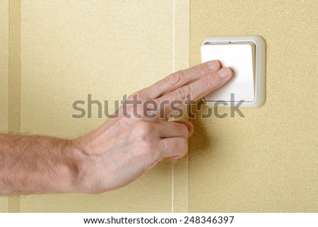 Two fingers switching, in or off, the light wih a big square security electric interrupter - stock photo