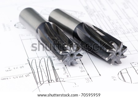 Two finished metal reamer tools with protective coating lying on blueprint drawing - stock photo