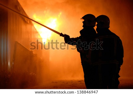 Two firefighters are trying to extinguish a hugh fire in a building  - stock photo