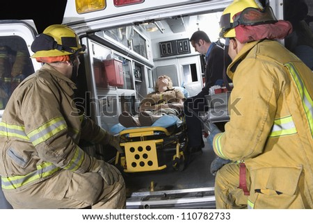 Two fireman looking at an injured person in an ambulance - stock photo