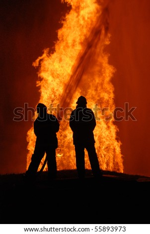 two firemen battling against raging fire, NOTE: top left corner particles are from fire and water spray, not camera noise - stock photo