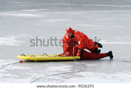 two firemen practicing rescue maneuvers on ice - stock photo