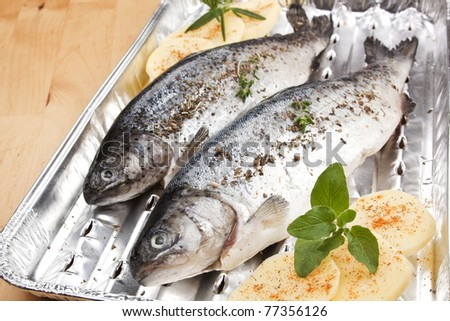 Two fish on grilling tray with potatoes and herbs prepared for grilling. Garlic and herbs in background. - stock photo