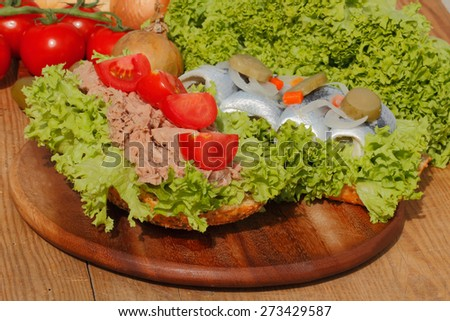 Two fish rolls with tuna and sour herring, garnished with lettuce, tomato, onion and pickles on a wooden board - stock photo