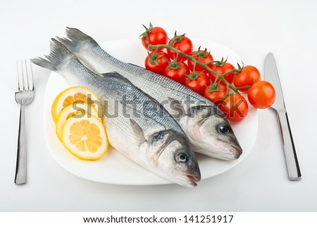 Two fish sea bass with lemon and tomato on a plate - stock photo