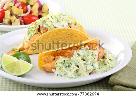 Two fish tacos topped with coleslaw and lime slices - stock photo