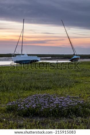 Two fishing boats on the salt marsh at Blakeney. - stock photo