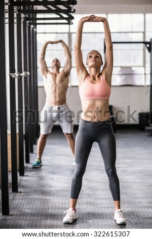 Two fit people doing fitness in crossfit gym - stock photo
