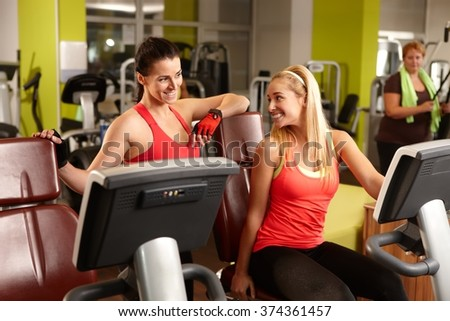 Two fit women talking in gym, exercising. - stock photo