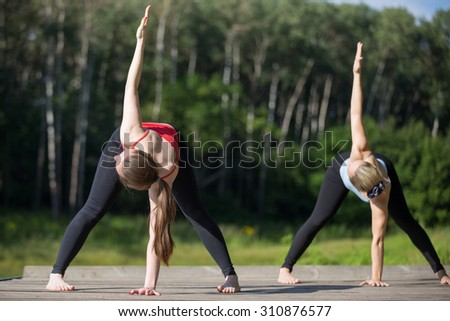 Two fit young beautiful women working out outdoors in park on summer day, wearing sportswear red and blue tank tops, standing in variation of Triangle yoga posture, full length - stock photo