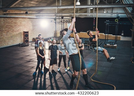 Two fit young men climbing ropes in a gym with people on the floor watching - stock photo