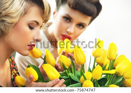 Two flower nymphs and a bunch of tulips - stock photo