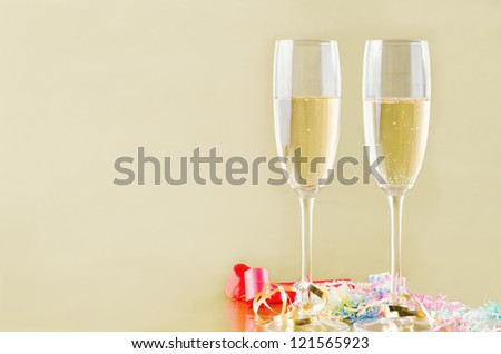 Two fluted champagne glasses with bubbles rising on a gold background with popper streamers and party horn blowers on the surface below.  Copy space to the left. - stock photo