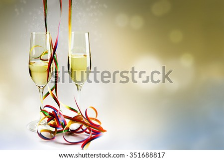 Two flutes champagne glasses and colorful streamers decoration against a bokeh background, concept for new years eve - stock photo