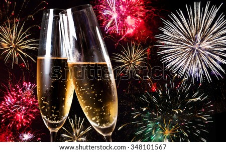 Two flutes of champagne over fireworks display - stock photo