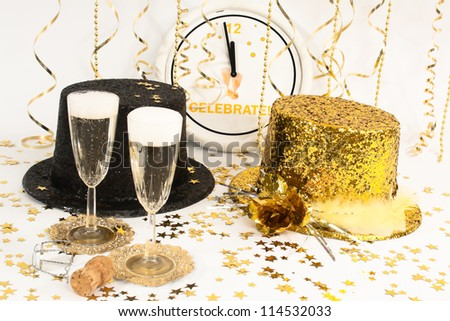 Two flutes of champagne, streamers  and glittery party hats  wait for the clock to reach midnight. - stock photo