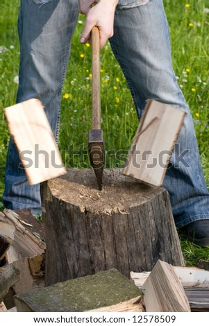 Two flying pieces of wood on log - stock photo