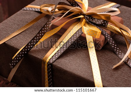Two foil gifts with yellow,gold,brown bows - stock photo