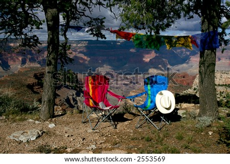 Two folding chairs and tibetan prayer flags on the edge of Grand Canyon - stock photo