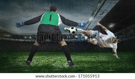 Two football players in action under rain in stadium - stock photo