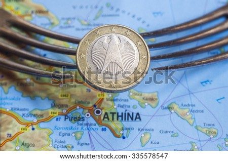 Two forks hold one euro coin over Greece map. - stock photo