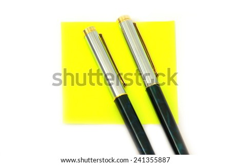 Two fountain pens and a yellow note - stock photo