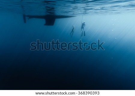 Two free divers training in the open sea along the anchor chain of the vessel - stock photo