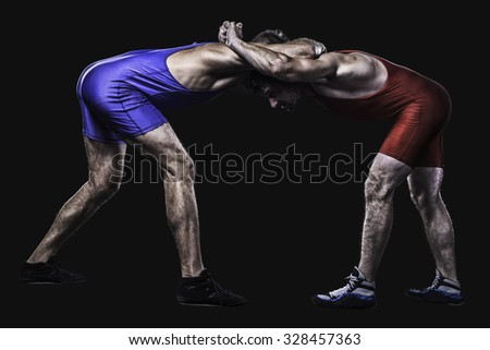 Two freestyle wrestlers in red and blue wrestling uniform isolated on black background - stock photo