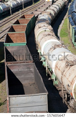 two freight trains with fuel cisterns and empty waggons - stock photo